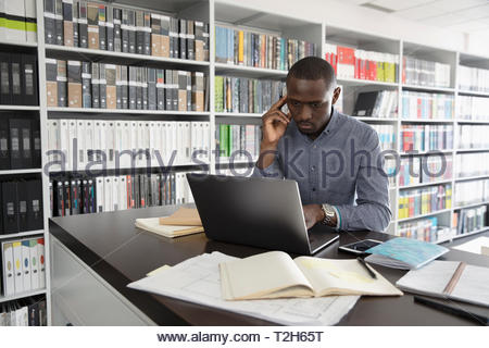 L'accent homme interior designer working at laptop in design studio Photo Stock