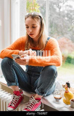 Jeune femme textos avec smart phone dans la fenêtre Photo Stock