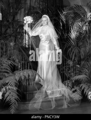 1930 PORTRAIT SMILING BRIDE en satin blanc robe de mariée ET VOILE FORME BOUQUET DE FLEURS DEBOUT SUR LES ESCALIERS AU MILIEU DE PLANTES FOUGÈRE - b14890 HAR001 HARS LUXE MARIÉS Mesdames pleine longueur SATIN VOILE MARIAGE PERSONNES PLANTES B&W suite nuptiale rêves de bonheur et d'excitation de l'AVENTURE BRIDES MARIAGE NOCES MARIAGE OCCASION RITE DE PASSAGE élégant robe de mariage MON MARIAGE MARIAGE FERN WOMAN NOIR ET BLANC AU MILIEU DE L'ORIGINE ETHNIQUE CAUCASIENNE HAR001 old fashioned Photo Stock