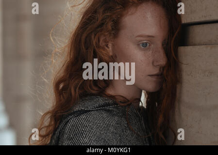 De graves Caucasian woman leaning visage sur pilier Photo Stock
