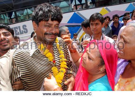 Un pèlerin qui a été sauvé et évacué d'Uttarakhand ravagé par les inondations, répond à ses proches à l'arrivée à Jodhpur, Rajasthan, India le 25 juin 2013. (Sunil Verma) Photo Stock