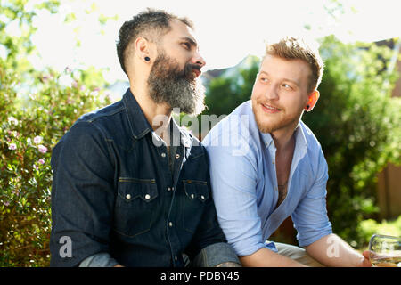 Homme gay couple talking in garden Photo Stock