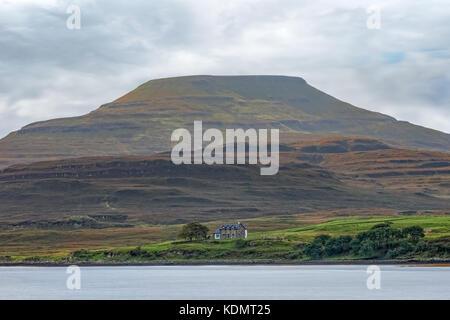 Un chalet un les rives d'un fleuve, dans l'ombre d'une colline sombre Photo Stock