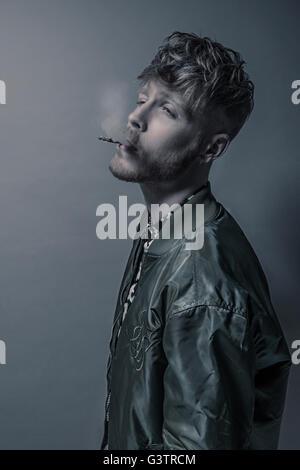 Studio portrait d'un jeune homme barbu de fumer une cigarette. Photo Stock