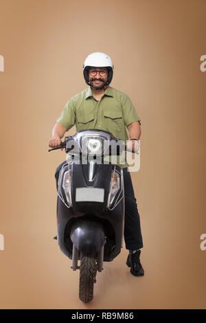 Smiling man sitting on a scooter le port de casque. Photo Stock