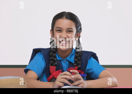 Portrait of smiling girl in school uniform studying at table Photo Stock