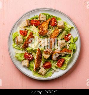 Salade césar avec viande de poitrine de poulet sur fond rose Photo Stock