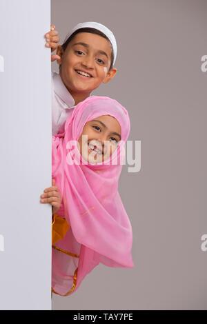 Jeune musulmane et le garçon, à l'arrière le mur Photo Stock