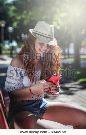 Une jeune femme en utilisant son téléphone portable tout en étant assis sur un banc Photo Stock