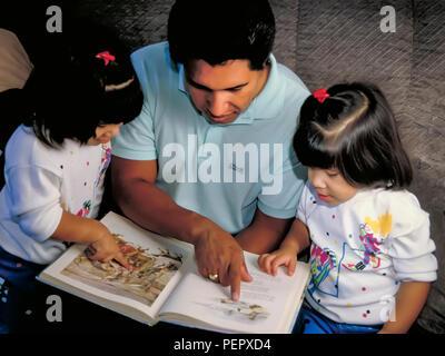 Héritage Mexicain père lecture storybook avec filles jumelles soeurs. M. © Myrleen Pearson ...Ferguson Cate Photo Stock