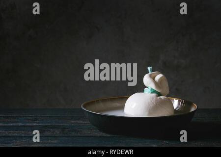 Bol à l'ensemble de fromage italien lié à la saumure de burrata sur planche en bois table. Style rustique foncé Photo Stock