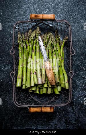 High angle close up de l'asperge verte fraîchement cueillie dans panier métal. Photo Stock