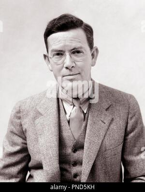 1930 PHOTOGRAPHE PORTRAIT MAN H. ARMSTRONG ROBERTS portant des lunettes gilet costume cravate LOOKING AT CAMERA - p5505 HAR001 HARS, CONTACT AVEC LES YEUX LE BONHEUR SOURIT STYLES costume trois pièces H ARMSTRONG ROBERTS ÉLÉGANT JOYEUSE FASHIONS NOIR ET BLANC DE L'ORIGINE ETHNIQUE CAUCASIENNE HAR001 old fashioned Photo Stock