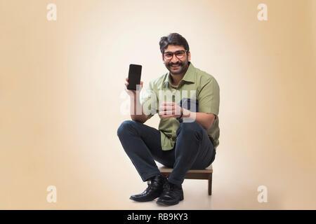 Smiling man wearing eyeglasses montrant un téléphone mobile tout en tenant une petite pochette et un verre de thé. Photo Stock