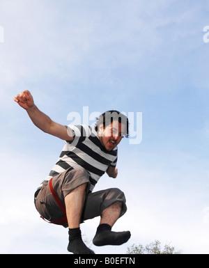 Homme âgé de 30 à 35 sautant avec ciel bleu en arrière-plan Photo Stock