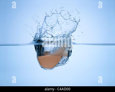 Une tasse de thé a chuté dans l'eau Photo Stock