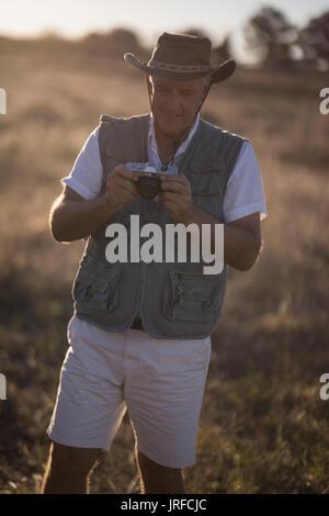 L'examen de l'homme photo sur appareil photo pendant des vacances de safari Photo Stock