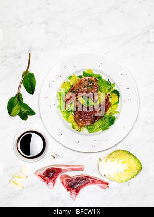 Côtelettes d'agneau et salade, un repas léger adapté pour la perte de poids, avec des ingrédients Photo Stock