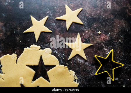 High angle close up de cookies en forme d'étoile coupé de la pâte. Photo Stock