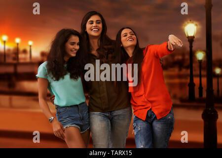 Trois amis s'amuser ensemble standing outdoors Photo Stock