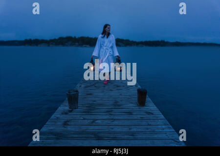 Une femme à lanterne on jetty Photo Stock