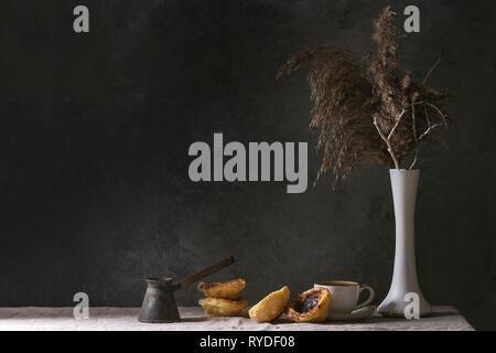 Tarte aux oeufs traditionnels portugais dessert Pasteis de nata Pastel avec tasse de café noir debout sur le linge de table cloth près de mur gris foncé. Photo Stock