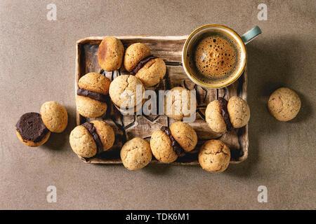 Baci di dama cookies biscuits noisette italienne maison avec crème au chocolat servi dans le bac en céramique avec tasse de café espresso brown au bac de texture Photo Stock