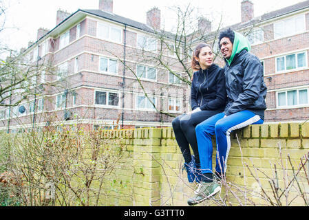 Un jeune couple assis sur un mur ensemble dans Southwark Park à Londres. Photo Stock