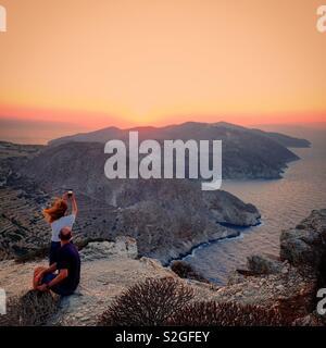 Couple de touristes en regardant le coucher du soleil, l'île de Folegandros Folegandros, Grèce Photo Stock