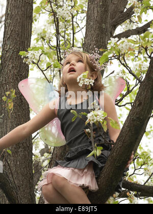 Little girl in fairy wings escalade un arbre Photo Stock