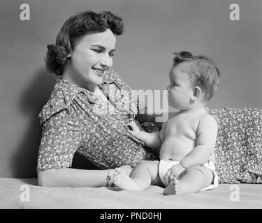 1940 WOMAN MOTHER SMILING AT BABY DAUGHTER SITTING UP - b8105 HAR001 STYLE HARS BÉBÉ COMMUNICATION HEUREUX JOIE SATISFACTION DE VIE SANTÉ VIE FEMELLES ACCUEIL pleine longueur, mi-longueur MESDAMES FILLES PERSONNES PRENANT SOIN B&W FORCE SOURIRES JOYEUX BONHEUR INCLINABLES CONNEXION CROISSANCE ÉLÉGANT JOYEUX MINEURS MID-ADULT MID-ADULT WOMAN MAMANS ENSEMBLE DÉTENTE NOIR ET BLANC bébé fille l'origine ethnique caucasienne HAR001 old fashioned SITTING UP Photo Stock