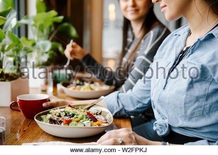 Les femmes de manger des salades dans restaurant Photo Stock