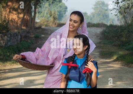 Female farmer ou rural femme marche sur village-rue, avec sa fille va à l'école portant un fer à repasser gold pan à la route. Photo Stock