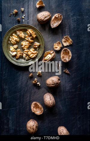 Coquilles de noix et sur fond de bois noir avec copie espace Photo Stock
