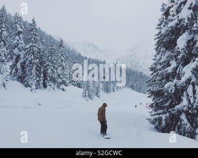 Personne snowboard sur une journée d'hiver enneigée très à la montagne. Photo Stock