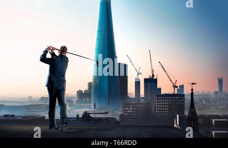 Businessman swinging golf club sur le toit de l'immeuble de la ville Photo Stock