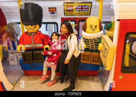 L'Angleterre, Londres, Leicester Square, Lego Store, les touristes asiatiques assis dans modèle Lego Train de métro de Londres avec Shakespeare et Garde côtière canadienne Photo Stock