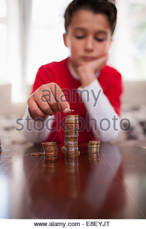 Smiling boy stacking coins Photo Stock