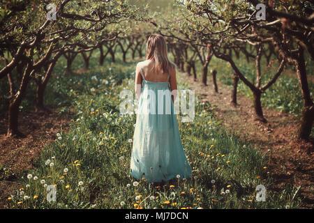 Femme dans un verger avec des fleurs. Comme l'effet de peinture Photo Stock