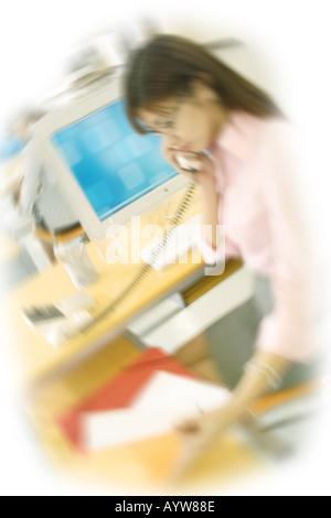 Femme parlant au téléphone au bureau Photo Stock