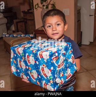 Jeune enfant cadeau de Noël d'enrubannage. Série de 7 images. M. © Myrleen Pearson ...Ferguson Cate Photo Stock