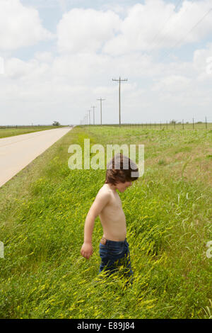 Boy walking in grass in countryside Photo Stock