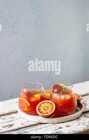Orange sanguine cocktails glacés dans les verres, décorés par tranche d'orange et menthe fraîche, servi dans le bac en céramique blanche sur table en bois avec mur gris à b Photo Stock