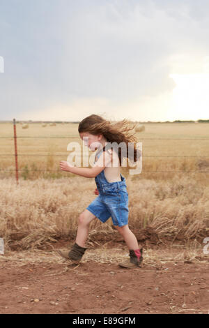 Fille courir le long de routes de campagne Photo Stock
