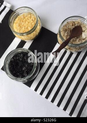 Trois pots de verre avec différents sels aromatisés, sur un plateau à rayures noir et blanc. Photo Stock
