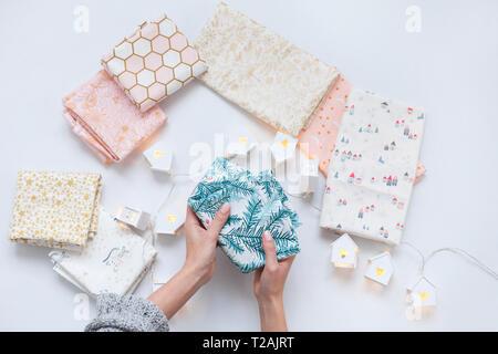 Woman's hands holding tissu avec des frondes de pin imprimer Photo Stock
