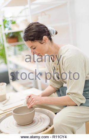 Vue latérale d'une femme se concentrer lors de la création de la poterie Photo Stock