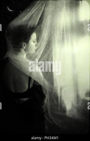 Triste femme debout par la fenêtre dans l'obscurité. Photo Stock