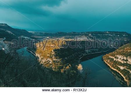 Vue panoramique d'une rivière au milieu des montagnes dans le soleil Photo Stock