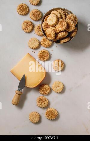 Snack-maison fromage sablés biscuits de sésame dans un bol et morceau de fromage à pâte dure avec couteau sur fond de marbre blanc. Mise à plat, de l'espace Photo Stock